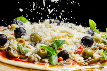 Falling cheese on a freshly prepared pizza on black background