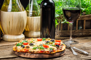 Homemade baked pizza served with wine