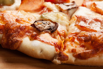 Closeup of pizza with ham, cheese and mushroom