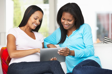Two Women Sitting On Sofa With Tablet Computer