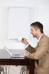 geschäftsmann trinkt kaffee am laptop