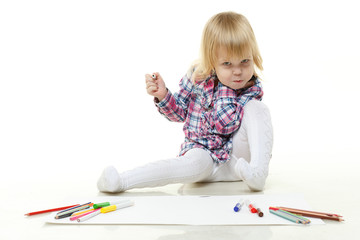 Happy little girl draws a picture.