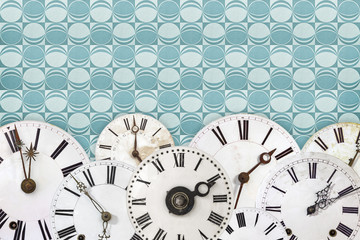 Set of vintage clock faces against a retro wallpaper background