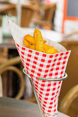 French fries in red and white blocked paper bag on table outdoor