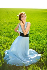 A young woman in a long blue dress enjoying a sunny day