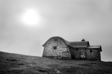 Wall Mural - Shelter in mountain in the morning with fog and sun