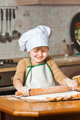 lovely girl in a chef's hat cooking sweet cake