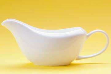 White ceramic gravy boat on a yellow background