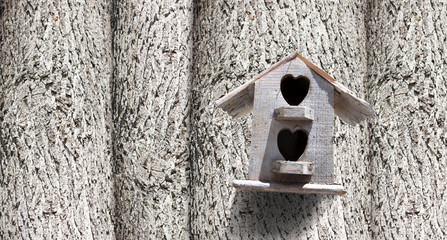 Bird house with the entrance hole with trees.