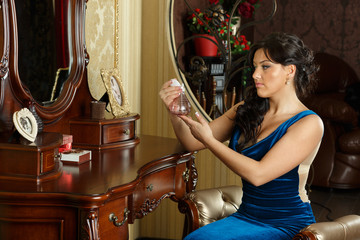 Young woman in evening dress with perfume.