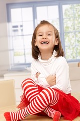 Happy little girl laughing in tailor seat