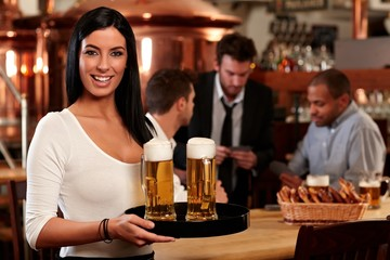 Happy young waitress with beer