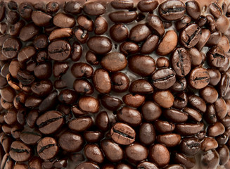 Coffee background. Heap of bronze coffee grains