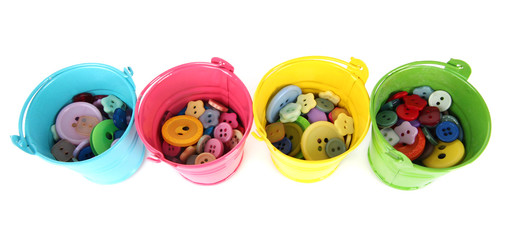 Colorful buttons in buckets isolated on white