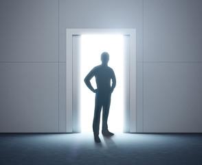 Silhouette of a man. Shining doorway