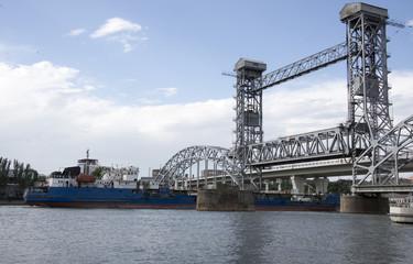 The ship floats under a drawbridge