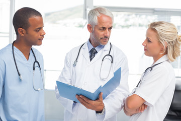 Three doctors examining a file