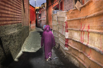 Woman in traditional crimson dress in Marrakesh street
