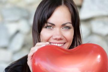 Glückliche Frau mit Herzluftballon
