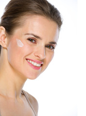 Beauty portrait of happy young woman with creme on cheek