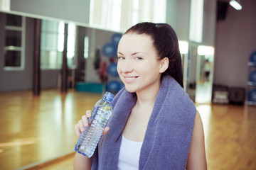 Young woman at the gym drinks water