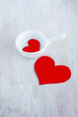 Two red hearts in the white gravy boat and on the wood board