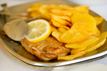 fried meat with potato and lemon