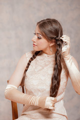 Vintage romantic fashion brunette woman. Doing her hair. Marble