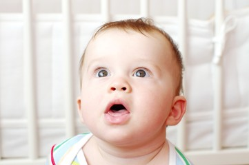 surprised baby against white bed