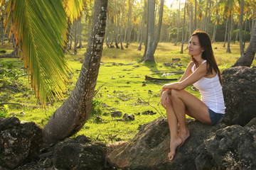 Young woman sitting on rocks in coconut trees grove, Las Galeras