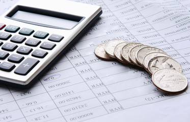 coins and calculator on business paper