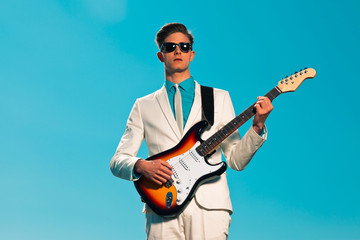 Retro fifties male electric guitar player wearing white suit and