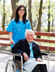 Walking With Senior Patient In Wheelchair