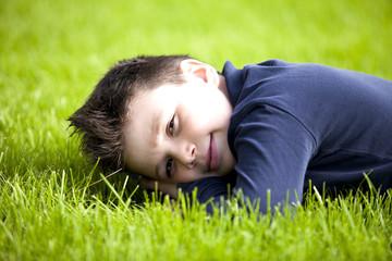 Bambino sdraiato sul prato verde