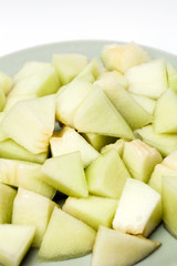 Melon sliced in small pieces served on a plate,