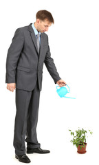 Young businessman watering pot isolated on white