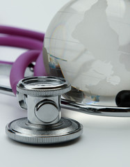 Stethoscope next to glass globe world map