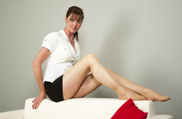 Woman sitting on the back of a white settee