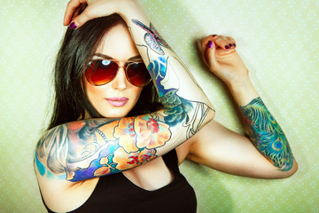 Beautiful girl with stylish make-up and tattooed arms..