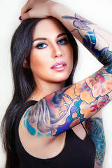 Beautiful girl with stylish make-up and tattooed arms.