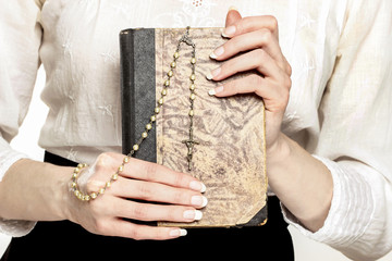 Holy Bible and white rosary in beautiful hands