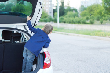 Child standing in the open trunk of a car