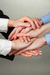 Group of young people's hands on gray background