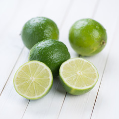 Fruits: fresh ripe limes on wooden boards, studio shot