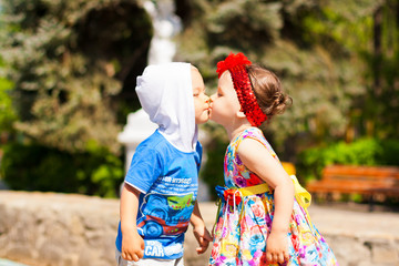 Little boy and little girl kissing in the park