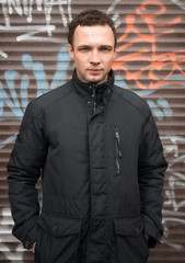 Caucasian man in black jacket with graffiti
