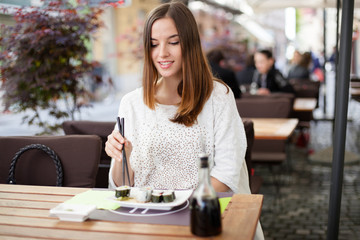 Young woman eating sushi in a restaurant