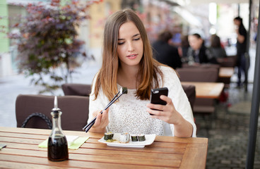 Young woman reading a message while eating sushi in a restaurant
