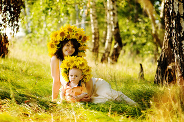 beautiful woman with son sitting down on green grass field