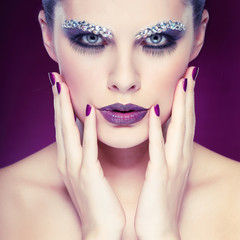 beautiful girl with strasses on face, on a violet